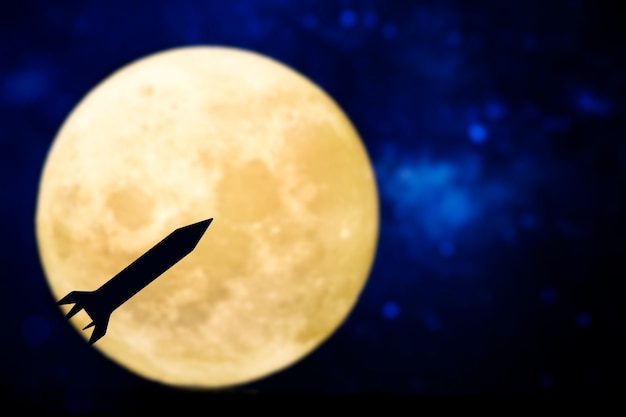 Silhueta de foguete sobre a lua cheia