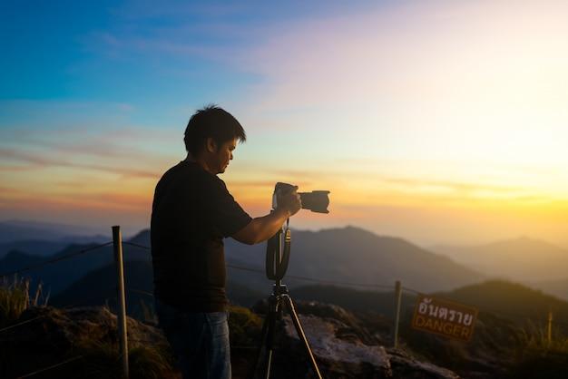 Silhueta de fotógrafo acima de um mar de nuvens, montanhas enevoadas