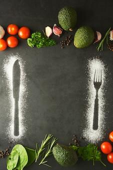 Silhueta de garfo e faca, feita com farinha em fundo escuro