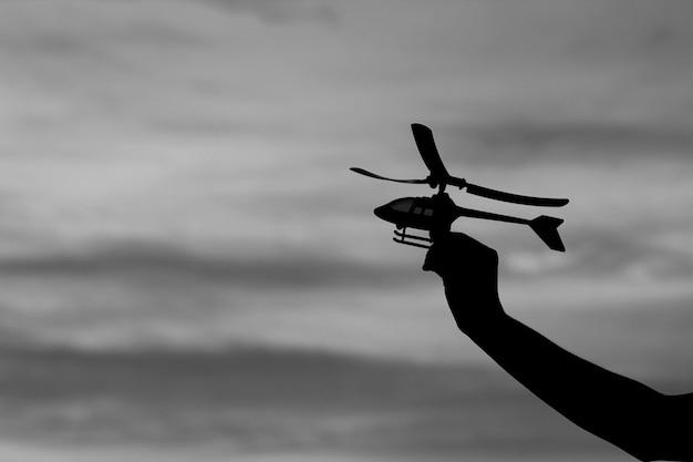 Silhueta de helicóptero de brinquedo em sonho de mão