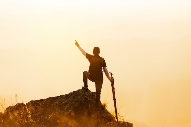 Silhueta de homem aguenta as mãos no pico da montanha, conceito de sucesso