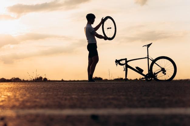 Silhueta de homem ativo em silhueta consertando bicicleta em estrada pavimentada