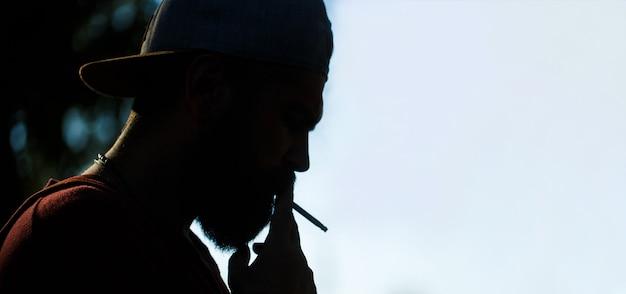 Silhueta de homem barbudo com charuto. homem de barba e bigode fumam charuto. charutos fumegantes. homem fumando, fume charuto. silhueta de homem fumando com barba. homem jovem hippie fuma.