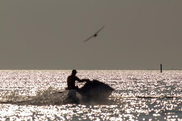 Silhueta de homem borrado no jetski