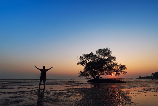 Silhueta de homem de viagem, levantando as mãos com seascape e fundo de árvore