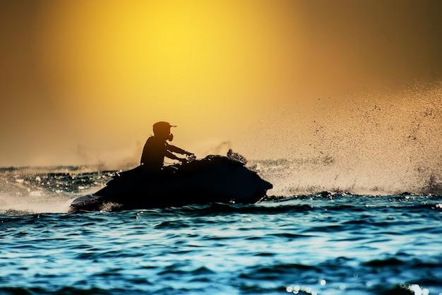 Silhueta de homem dirigir freestyle jet ski ao pôr do sol. piloto profissional fazer truques no mar
