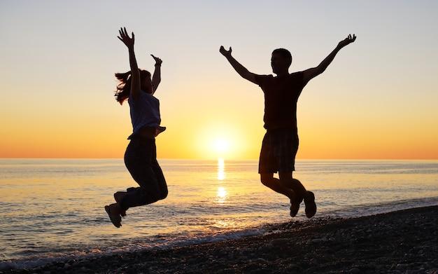 Silhueta de homem e mulher pulando de alegria ao pôr do sol na praia deserta do mar