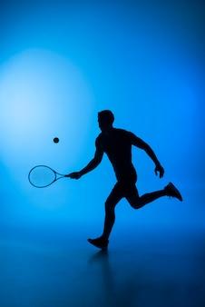 Silhueta de homem jogando tênis, tacada completa