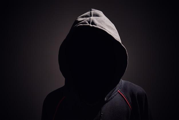 Silhueta de homem sem rosto no capuz em um preto.