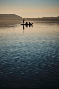 Silhueta de homens pescando em um barco em um lago durante o pôr do sol