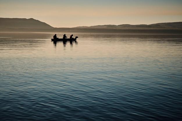 Silhueta de homens pescando em um barco perto da costa durante um pôr do sol