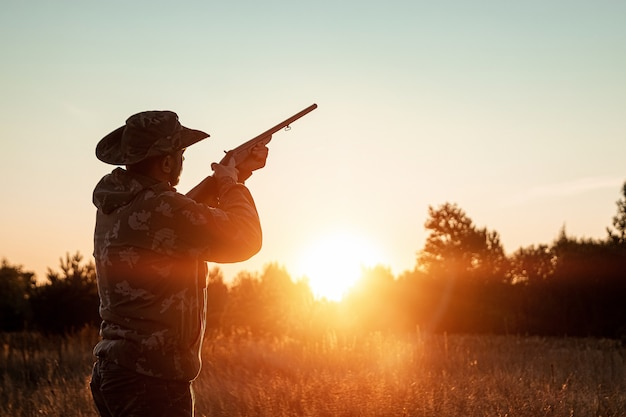 Silhueta de hunter em um chapéu de cowboy com uma arma nas mãos em um belo pôr do sol