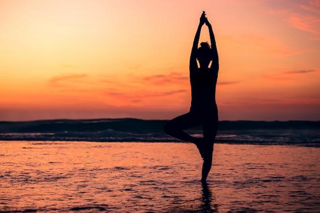 Silhueta de ioga meditação de mulher na praia do mar ao pôr do sol