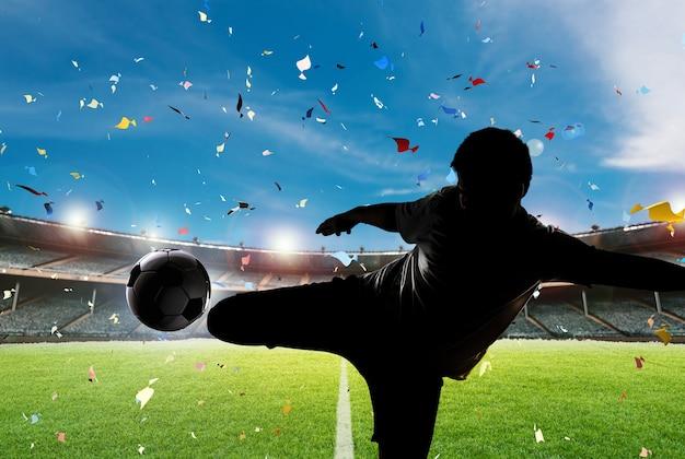 Silhueta de jogador de futebol chutando a bola com o fundo do estádio