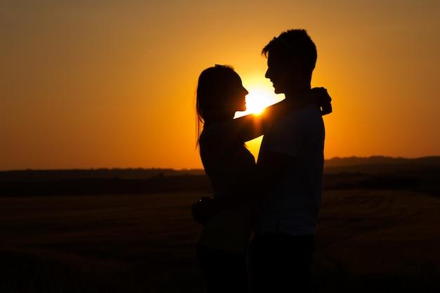 Silhueta de jovem casal no campo.