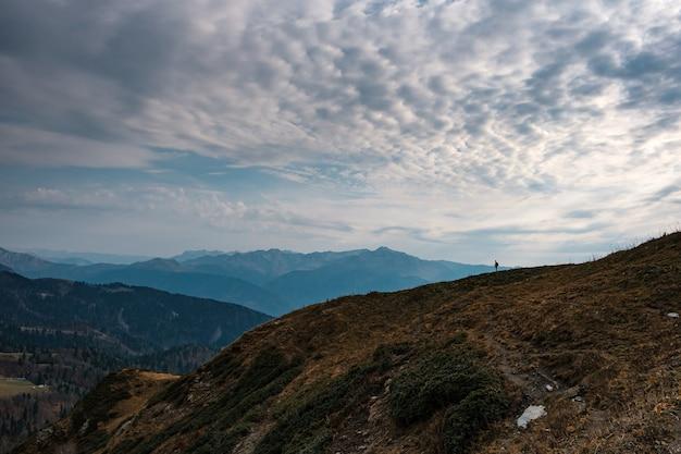 Silhueta de jovem hippie masculino nas montanhas no outono. conceito de destino de viagens de descoberta. turista no fundo de pedras altas. esporte e conceito de vida ativa.