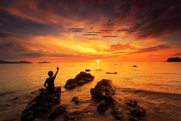 Silhueta de jovem mostrar a mão de amor e pé na rocha no mar com o céu do sol