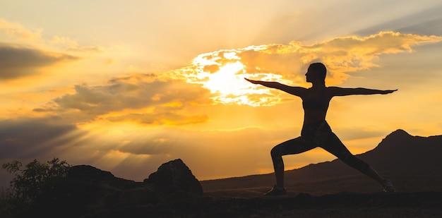 Silhueta de jovem praticando ioga ao pôr do sol