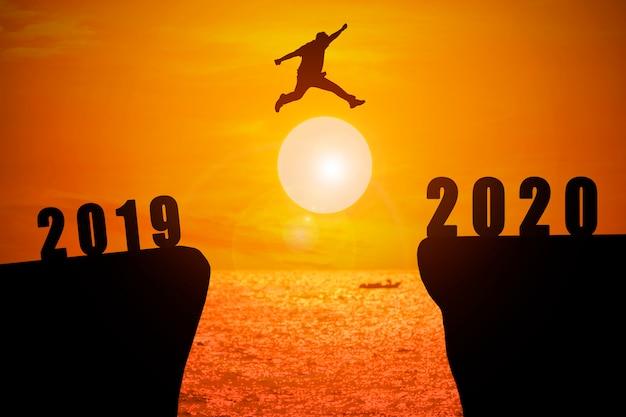 Silhueta de jovem pulando do ano 2019 ao ano 2020 com fundo de nascer do sol