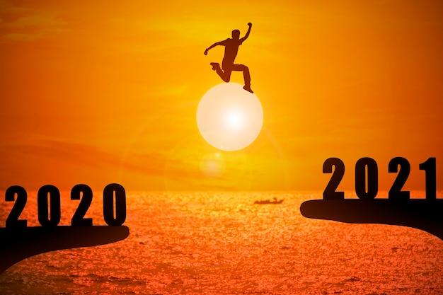 Silhueta de jovem pulando entre 2020 e 2021 anos com belo pôr do sol no mar.