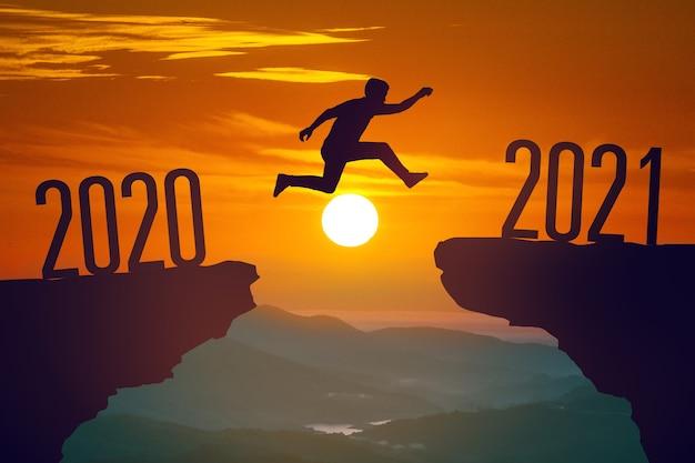 Silhueta de jovem pulando entre 2020 e 2021 anos com o pôr do sol