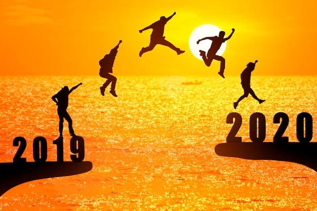 Silhueta de jovens empresários pulando de 2019 a 2020