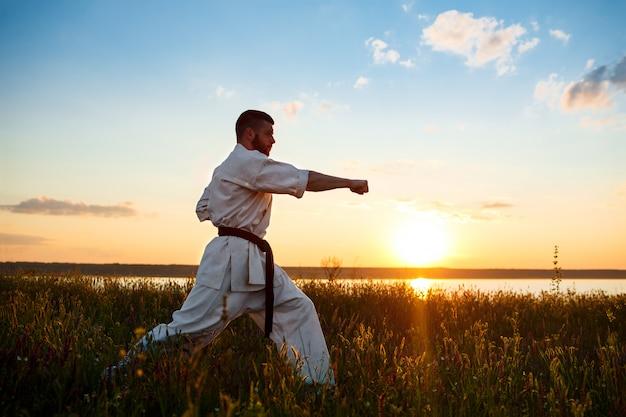 Silhueta de karatê de treinamento esportivo homem em campo ao nascer do sol.