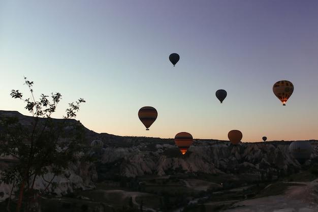 Silhueta de lindos balões de ar quente ao nascer do sol na capadócia
