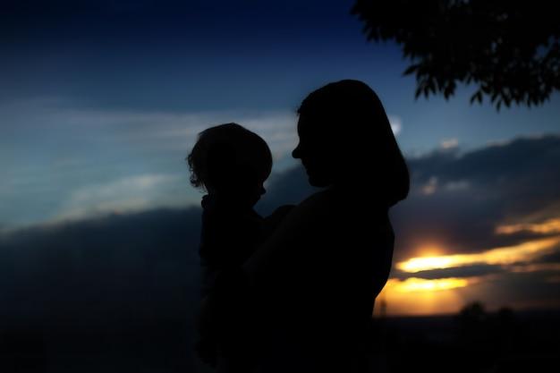Silhueta de mãe com seu bebê contra o pôr do sol ao ar livre. mãe e filho pequeno estão se abraçando