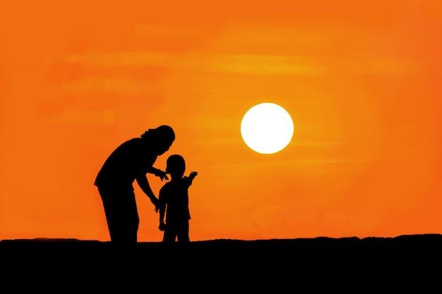 Silhueta de mãe e filho em pé na montanha, observando o pôr do sol.