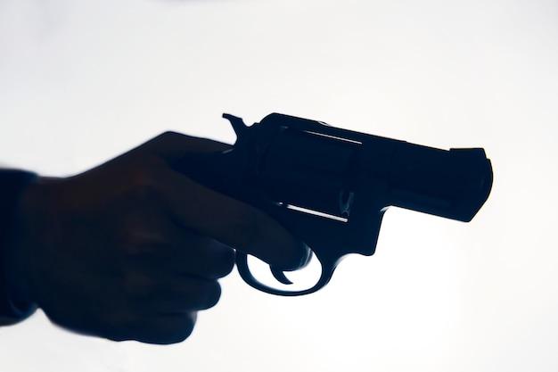 Silhueta de mão do homem com revólver em armas de fogo de fundo branco para defesa ou ataque criminoso com ...