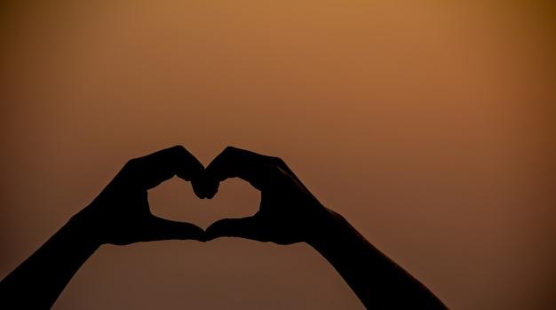 Silhueta de mão em forma de coração com pôr do sol