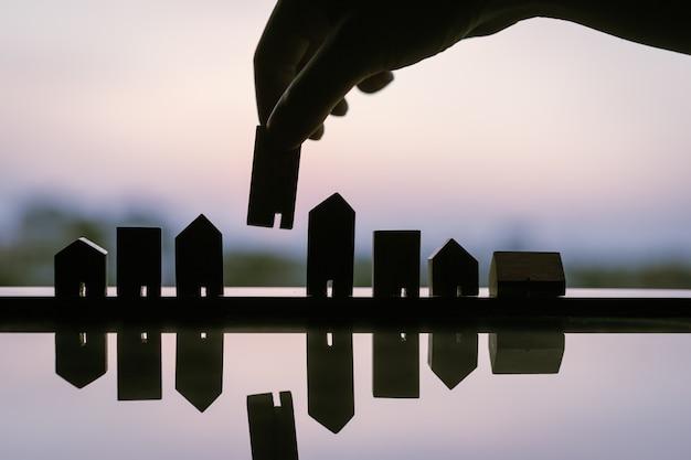 Silhueta de mão escolhendo mini modelo de casa de madeira