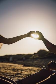 Silhueta de mãos formando coração