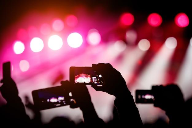 Silhueta de mãos usando smartphones para tirar fotos e vídeos em show de música ao vivo.