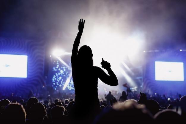 Silhueta de menina curtindo o festival de música, concerto.