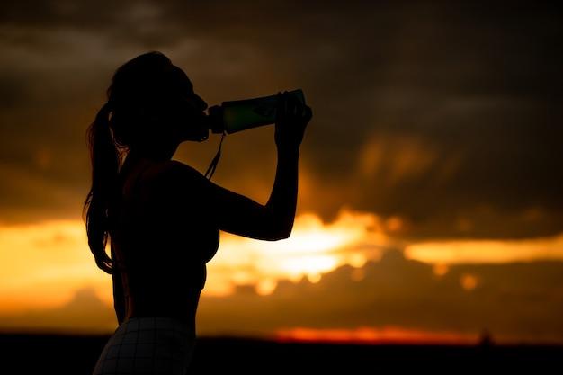 Silhueta de menina no sportswear bebe água de uma garrafa ao pôr do sol.