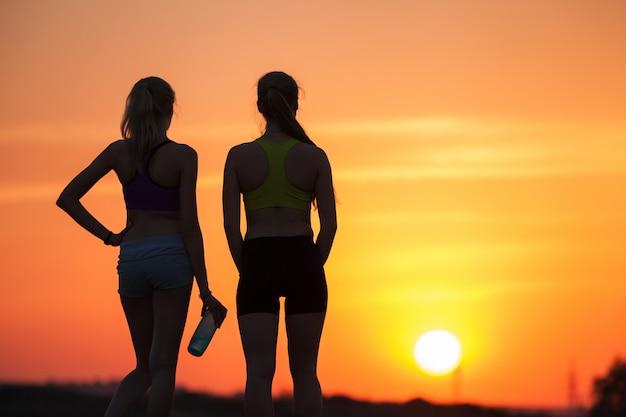 Silhueta de meninas ao pôr do sol