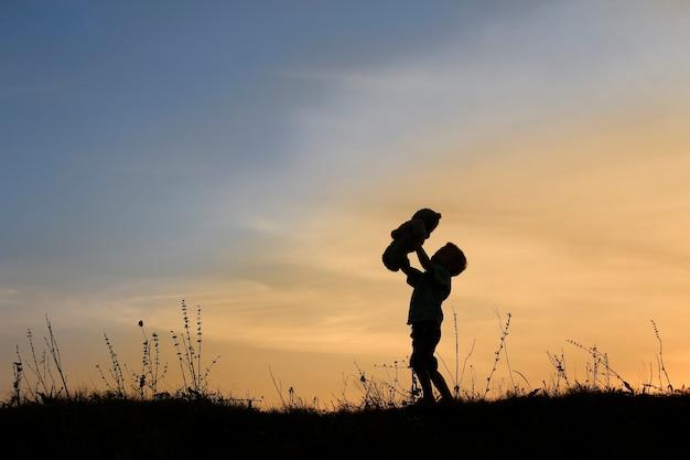 Silhueta de menino com urso no pôr do sol