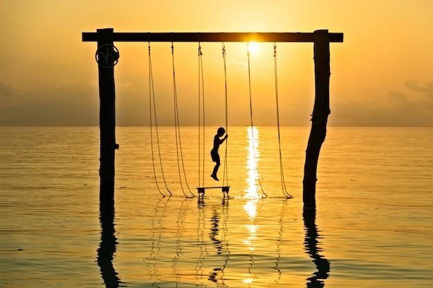 Silhueta de menino em balanço de corda sobre a paisagem por do sol das maldivas
