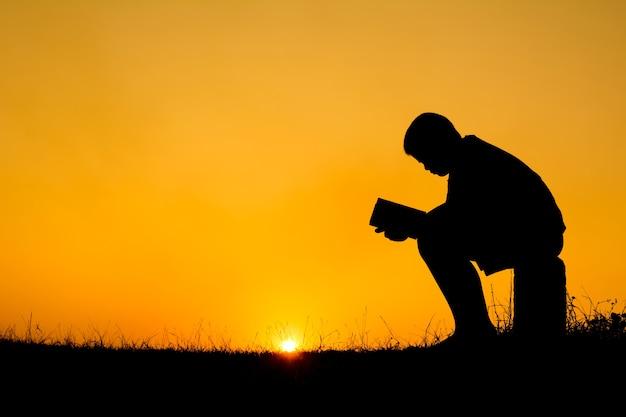 Silhueta de menino lendo um livro durante o fundo do sol do céu