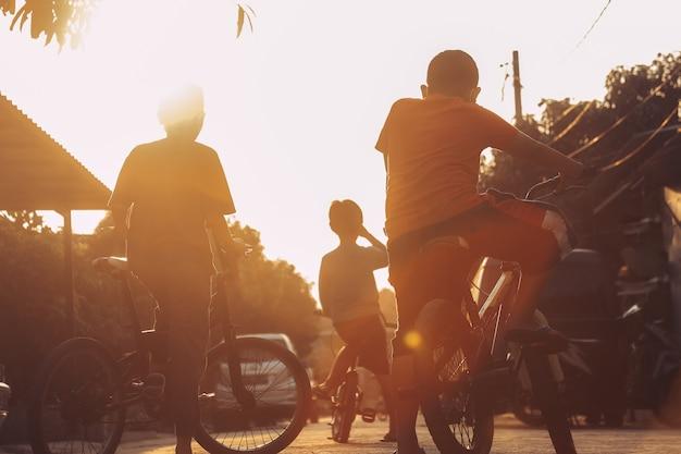 Silhueta de meninos andando de bicicleta ao ar livre durante o pôr do sol