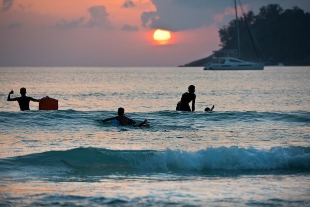 Silhueta de meninos surfando em pranchas na costa do oceano durante o pôr do sol