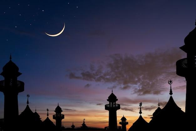 Silhueta de mesquitas em cúpula no céu ao anoitecer e na lua crescente com a religião islâmica para os muçulmanos