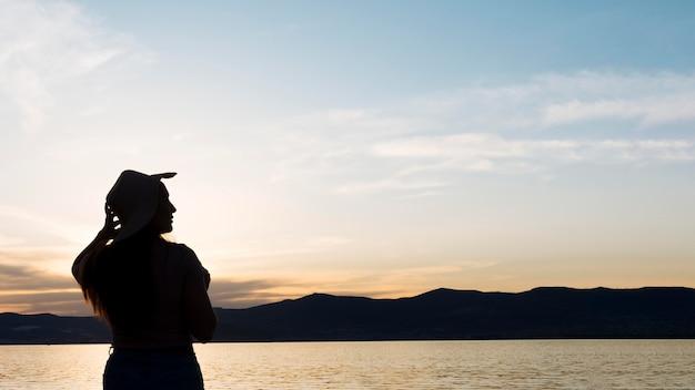 Silhueta de mulher ao pôr do sol com montanhas