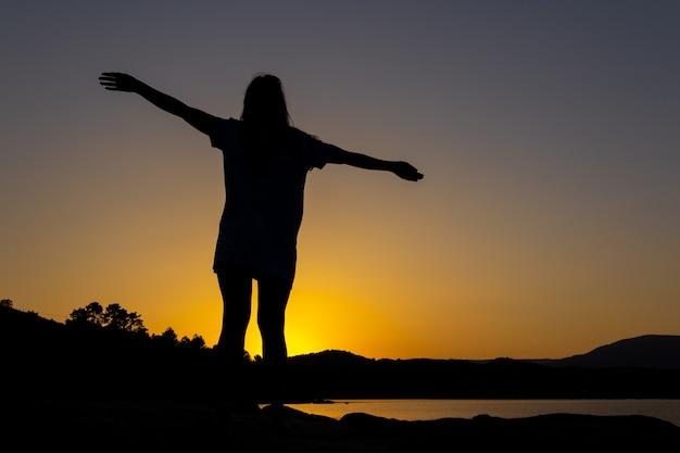 Silhueta de mulher ao pôr do sol com os braços estendidos superando as dificuldades da vida copie o espaço