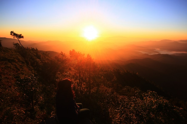 Silhueta de mulher asiática, sentada sozinha no nascer do sol dourado natural