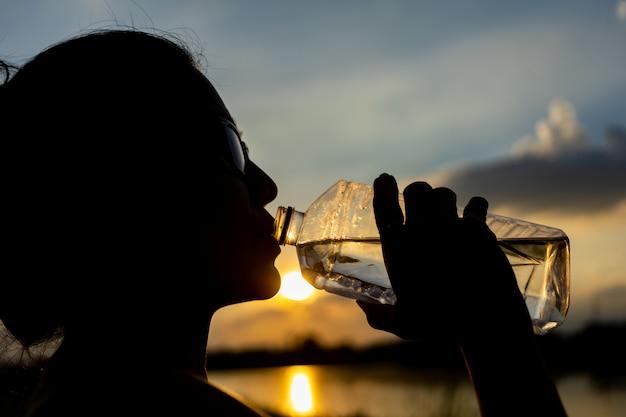 Silhueta de mulher beber água da garrafa ao ar livre à noite