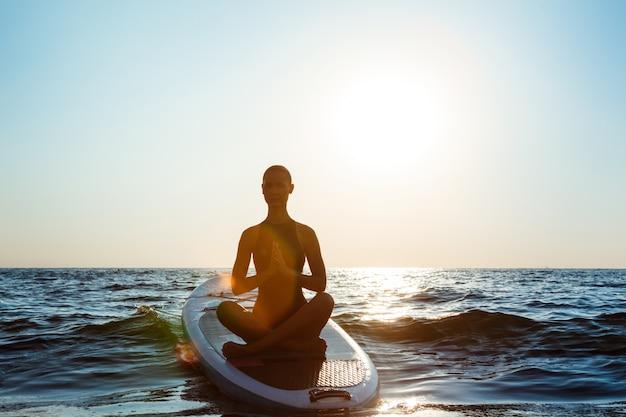Silhueta de mulher bonita praticando ioga na prancha de surf ao nascer do sol.