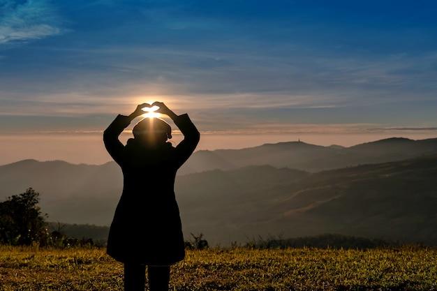 Silhueta de mulher com as mãos no símbolo do coração perto do nascer do sol na montanha
